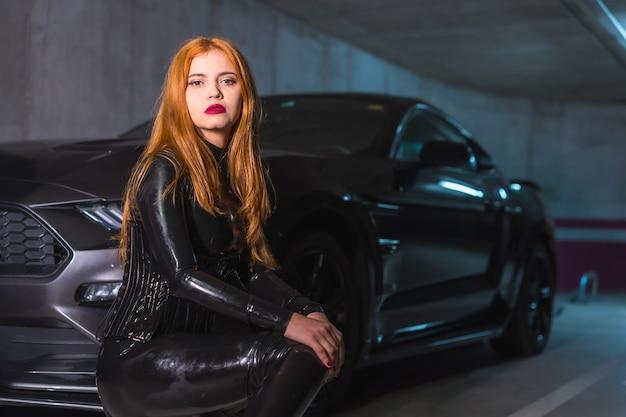 Ruiva de látex, blusa preta e calça justa com salto grande, agachada em um carro esporte em uma garagem com visual sedutor