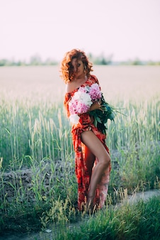 Ruiva de vestido vermelho com buquê de peônias dançando alegre no campo de trigo no verão ao pôr do sol. vertical