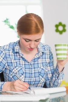 Ruiva, escrevendo no bloco de notas na mesa dela e segurando café
