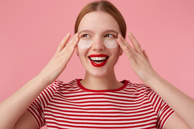 Ruiva fofa em uma camiseta listrada vermelha, com lábios vermelhos, toca seu rosto com os dedos, espera a ação mágica de manchas de olheiras sob seus olhos, aproveita o tempo livre para cuidar de si.