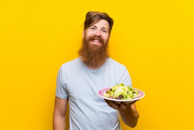 Ruiva homem com barba longa e com salada sobre parede amarela isolada sorrindo muito