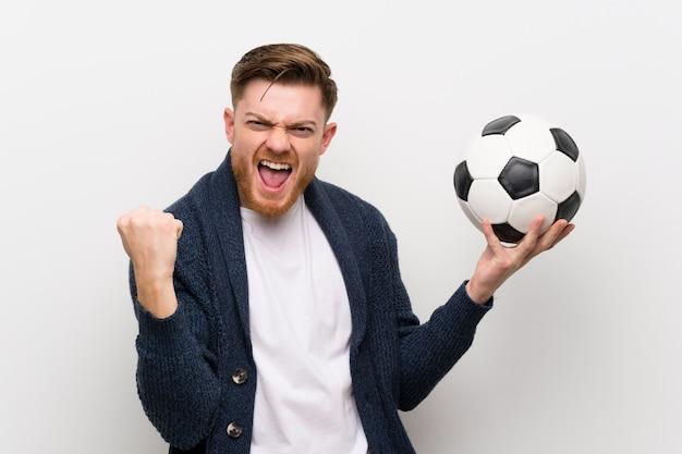 Ruiva homem segurando uma bola de futebol