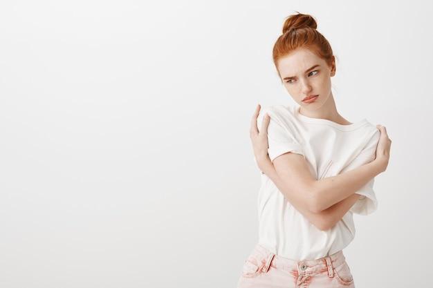 Ruiva insegura e ofendida se abraçando e parecendo zangada.