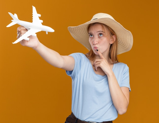 Ruiva jovem confusa e ruiva com sardas, usando um chapéu de praia, coloca o dedo no queixo e segura a modelo do avião, olhando para cima, isolada na parede laranja com espaço de cópia