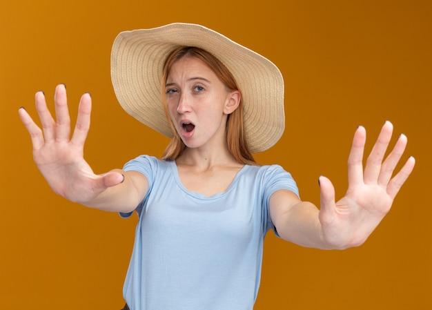 Ruiva jovem e desagradável com sardas e chapéu de praia estendendo as mãos