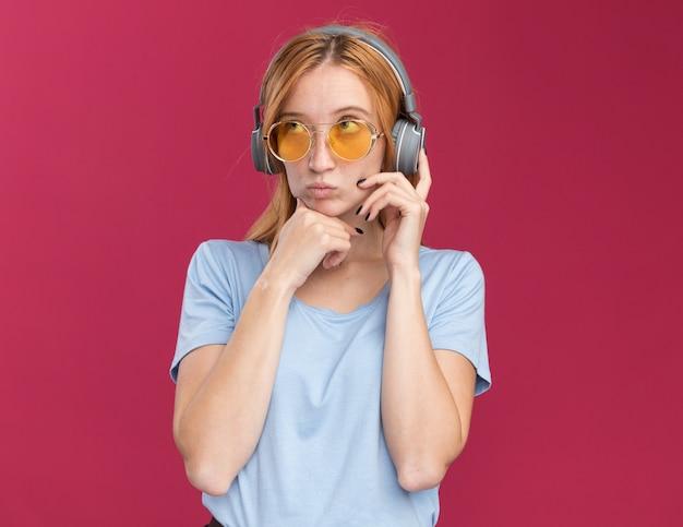 Ruiva jovem pensativa e ruiva com sardas em óculos de sol e fones de ouvido, segurando o queixo, olhando para cima, isolado na parede rosa com espaço de cópia