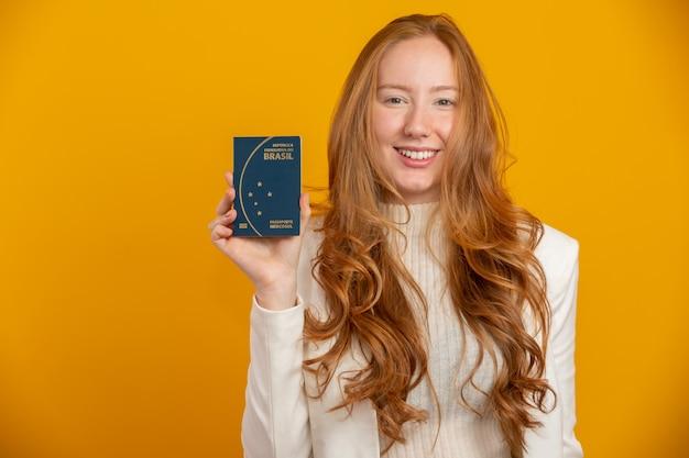 Ruiva linda garota de cabelos em viagem. próxima viagem. menina, segurando o passaporte brasileiro. em amarelo.