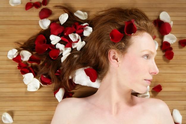 Ruiva linda mulher, pétalas de rosa no cabelo