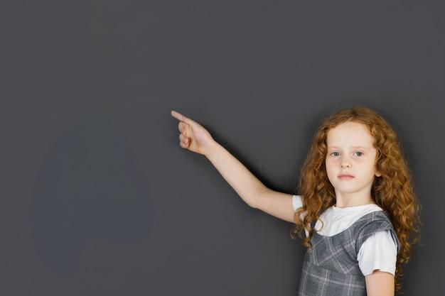 Ruiva menina apontando na lousa, em sala de aula