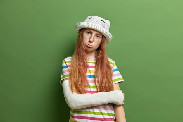 Ruiva ofendida descontente com rosto sardento, de mau humor após ter sofrido um trauma, inclina a cabeça e franze os lábios, usa chapéu e camiseta listrada, posa contra parede verde.