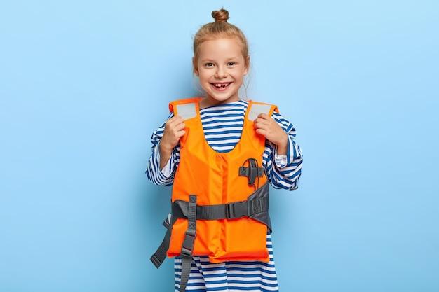 Ruiva pré-escolar posando com roupa de piscina