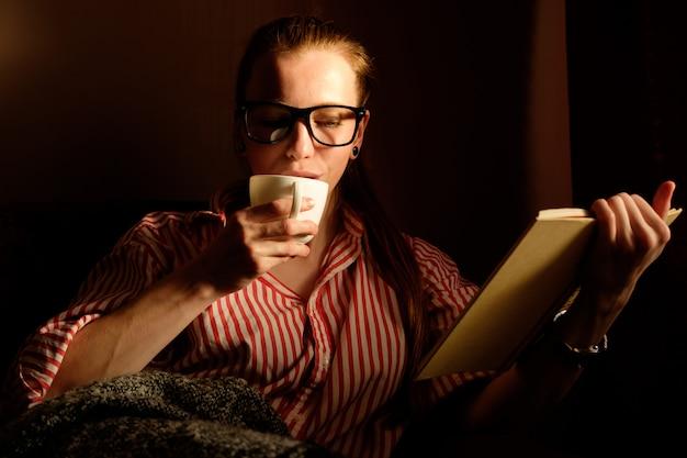 Ruiva ruiva na camisa despojada, lendo o livro, bebendo café, deitado no sofá e sorrindo