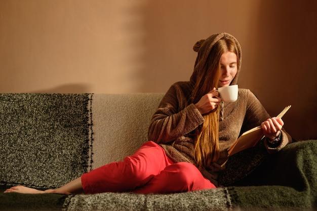Ruiva ruiva no livro de leitura engraçado com capuz, bebendo café, deitado no sofá e sorrindo