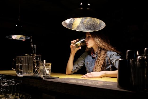 Ruiva sentada no bar (pub) bebendo coquetel gelado