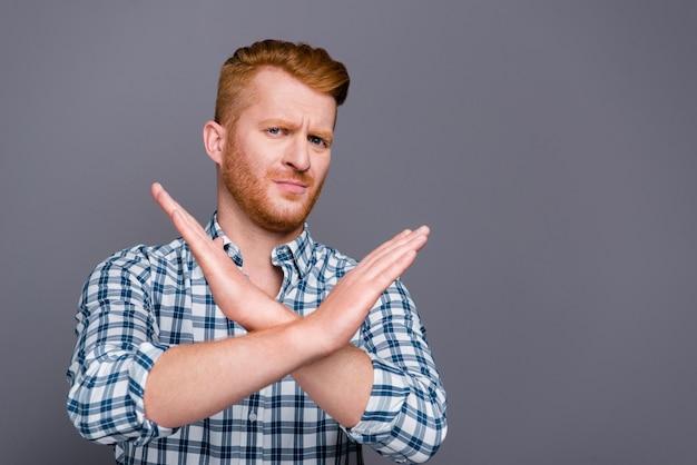 Ruivo com uma camisa xadrez azul posando contra a parede cinza