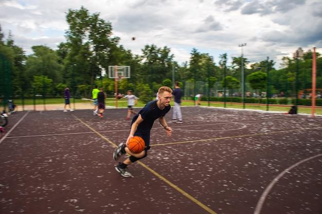 Ruivo jovem correndo e driblando uma bola de basquete em alta velocidade em um campo esportivo na rua durante o dia.