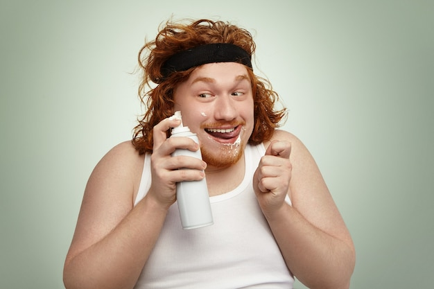 Ruivo manhoso e gordo usando faixa esportiva e regata segurando uma lata de spray, com um olhar louco e alegre