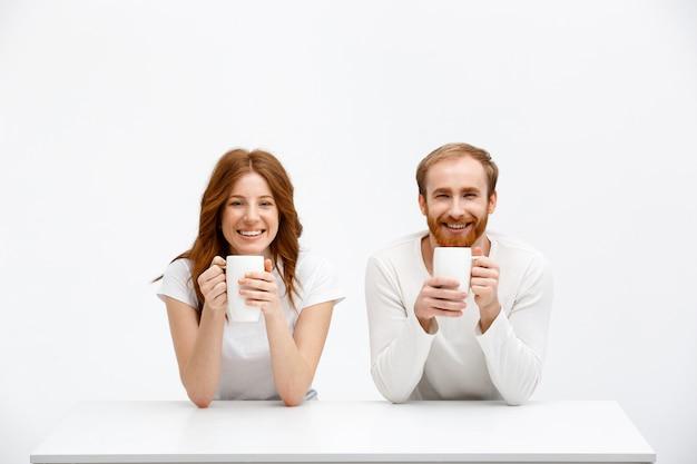 Ruivos de casal feliz bebem chá de xícaras