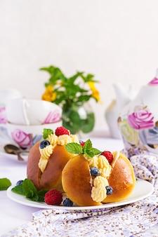 Rum pães da savana decorados com chantilly e frutas frescas