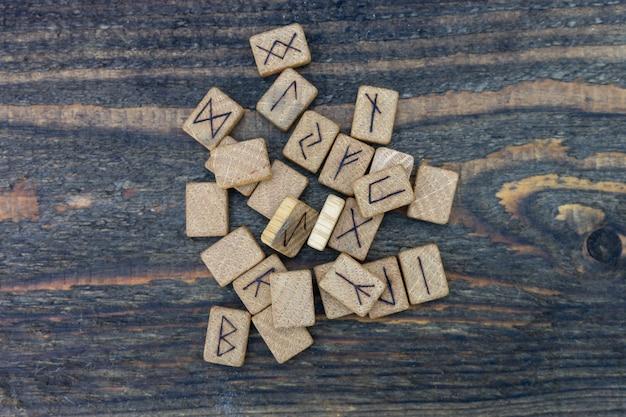 Runas de madeira escandinavas em uma mesa de madeira velha. élder futhark.