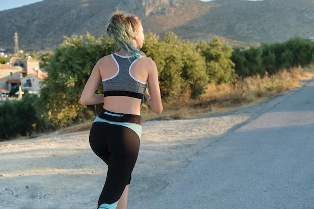 Running fitness girl em fones de ouvido com smartphone, vista traseira, espaço de cópia