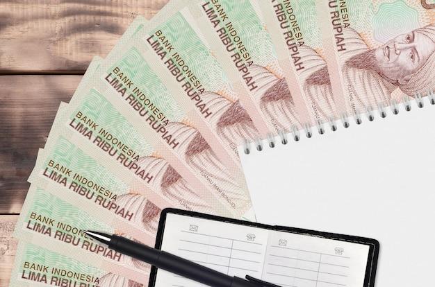 Rupia indonésia com leque de notas e bloco de notas com livro de contatos e caneta preta