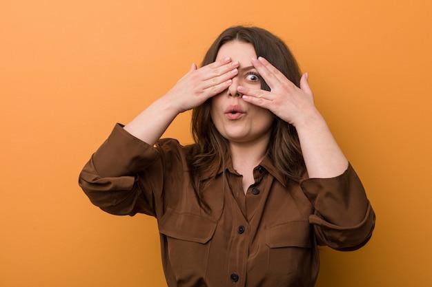 Russa mulher piscar curvilínea jovem por entre os dedos assustada e nervosa.