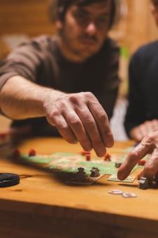 Rússia, dezembro de 2020: dois amigos homens se divertem jogando o jogo de tabuleiro carcassonne tarde da noite ou à noite. mãos masculinas e cartas de jogo e fichas na mesa