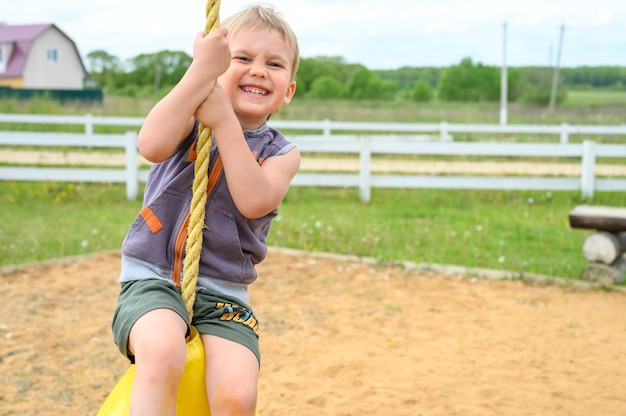 Rússia, maio de 2020 - menino feliz de quatro anos de idade balança em uma bola de balanço infantil ou uma pêra em uma corda em um parquinho em uma vila no interior no verão