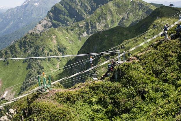 Rússia rosa khutor-16 de julho de 2021: turista caminha na ponte de corda.