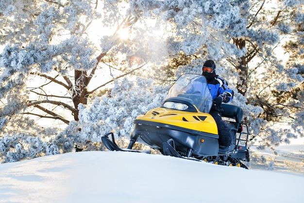 Rússia, sibiria, 24 de janeiro de 2019: homem em um snowmobile movendo-se na floresta de inverno no dia de inverno do nascer do sol