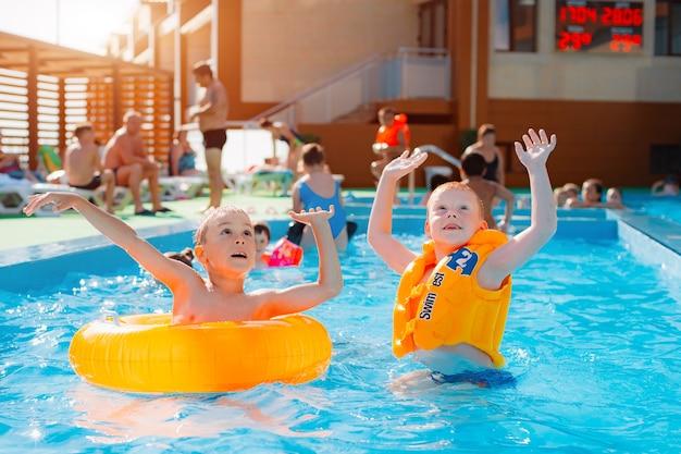 Rússia. tuapse. pensão avtotransportnik 19 de junho de 2020 braçadeiras infláveis infantis aprendendo a nadar na piscina externa do resort. jogos de armas de água para crianças.