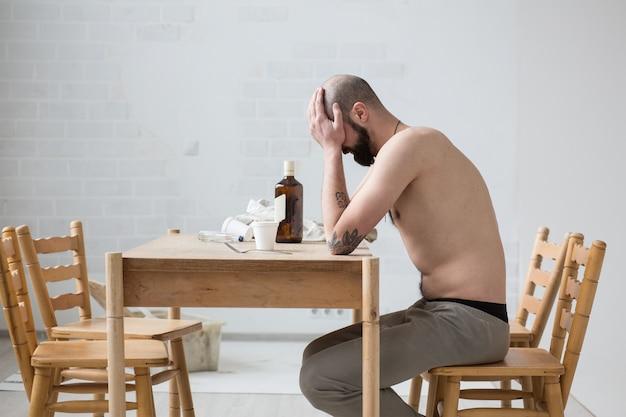 Russo bêbado sentado à mesa e triste. ela fecha o rosto