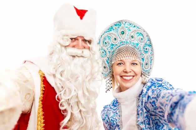 Russo papai noel com uma donzela de neve, sorrindo e tomando uma selfie. isolado sobre o fundo branco