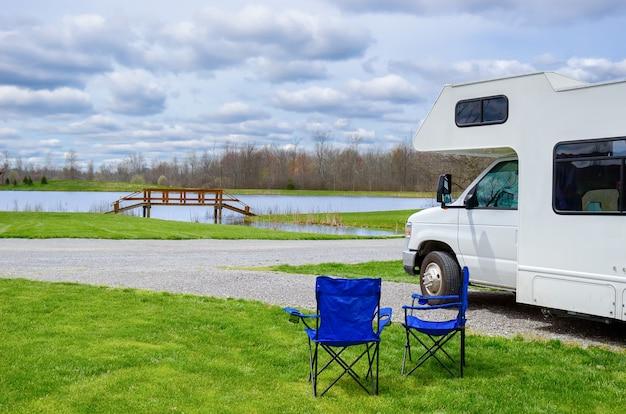 Rv (campista) e cadeiras em camping, viagens de férias com a família, viagem de férias no motorhome