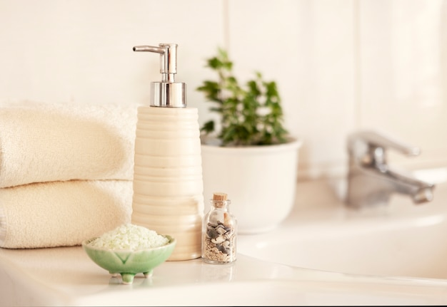 Sabão cerâmico, frasco de xampu, tigela com sal de banho e toalhas de algodão branco na superfície interior do banheiro turva com pia e torneira.