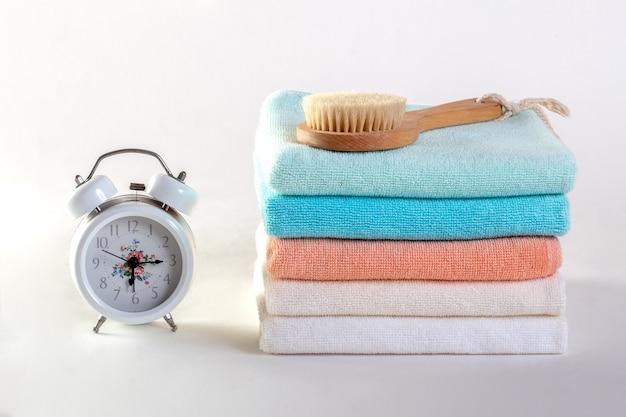 Sabão cerâmico, frascos do champô e toalhas brancas do algodão no fundo branco.