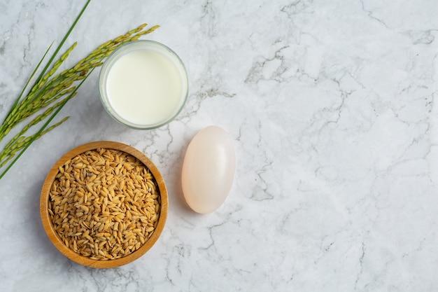 Sabão de arroz de leite, copo de leite, plantas de arroz e sementes de arroz colocados em piso de mármore branco