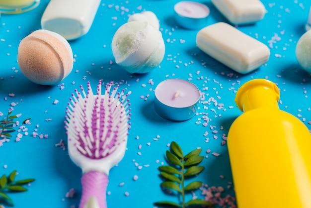 Sabão de banho com escova de cabelo e vela no fundo azul