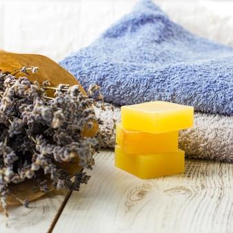 Sabão de lavanda natural e sal de banho, óleo francês e toalhas em um fundo branco de madeira