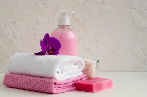 Sabão líquido e duas toalhas em um fundo branco.