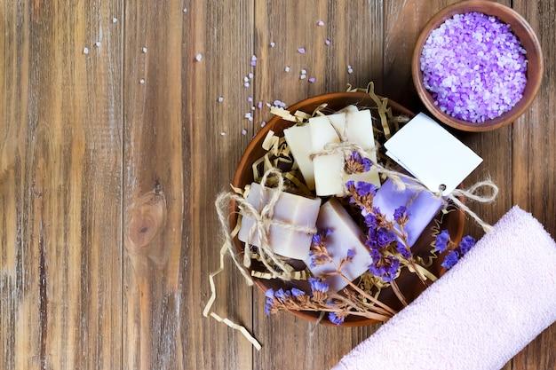 Sabão orgânico em uma cesta com flores secas e sal marinho natural em uma tigela na mesa de madeira marrom