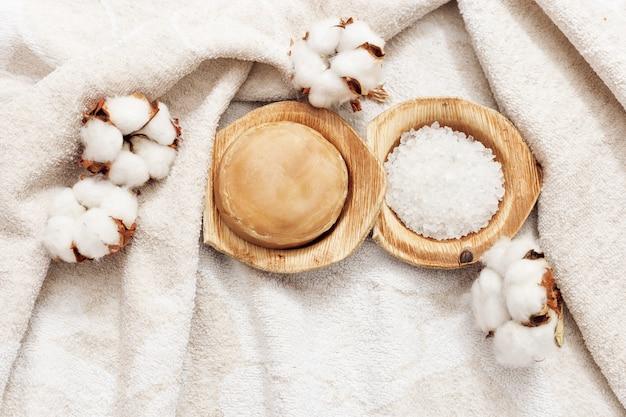 Sabão redondo, sal marinho na tigela, flores de algodão em terry bege