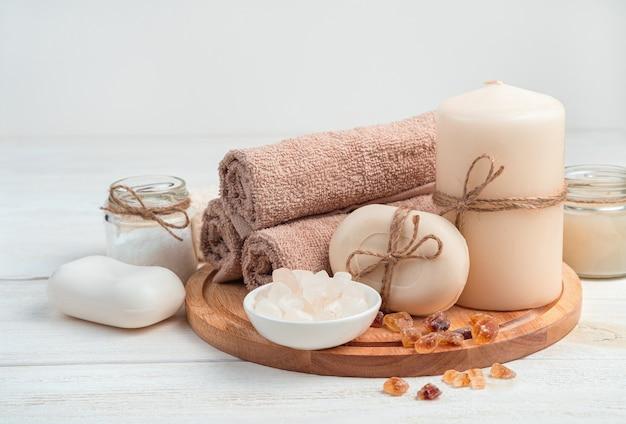Sabão, velas, toalha e sal em uma placa sobre um fundo branco de madeira. a vista lateral é horizontal. o conceito de tratamentos de spa.