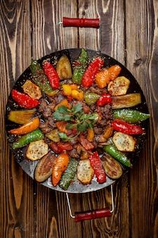 Sábio de carne grelhada com batatas, pimentão e berinjela