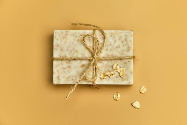 Sabonete artesanal de banho natural de aveia em fundo bege. sabão e flocos de aveia em uma tigela de madeira. barras de sabão. spa, cuidados com a pele e o corpo. embrulho para presente.