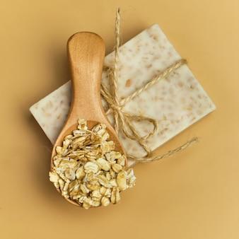 Sabonete artesanal de banho natural de aveia na superfície bege. sabão e flocos de aveia em uma tigela de madeira. barras de sabão. spa, cuidados com a pele e o corpo. embrulho para presente.