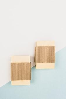 Sabonete artesanal de ervas em uma embalagem com fundo bicolor, close-up