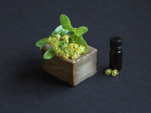 Sabonete artesanal e tília flores sobre uma mesa preta.