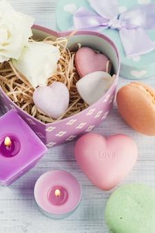 Sabonete, caixa de presente e vela acesa rosa